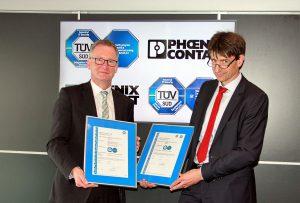 Phoenix Contact CTO Roland Bent (li.) nimmt die Zertifikate von Jens Butenandt (CTO Product Service, TÜV Süd) entgegen.
