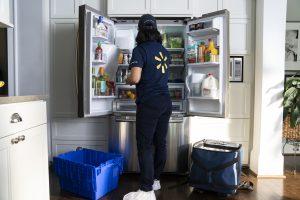 Eine Walmart-Mitarbeiterin befüllt den Kühlschrank eines Kunden.