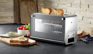 WMF präsentiert den neuen Lono Glas-Toaster. Dieser verfügt über entnehmbare Glasscheiben, die den Blick ins Innere gestatten, sowie über eine vollautomatische Bedienung auf Knopfdruck.