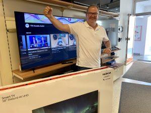 Thomas Edinger, Inhaber von Expert Edinger, freut sich über den Hauptgewinn beim TFK-Tippspiel zum Finale der Fußball-Europameisterschaft. Mit dem richtigen Tipp hat er einen NOKIA 5800A4 58Zoll 4K Android TV gewonnen.